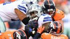 Dallas Cowboys running back Ezekiel Elliott  (centre) is tackled by the Denver Broncos defence. Photograph:  Ron Chenoy/ USA TODAY