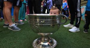 HIDE AND SEEK: Molly Brown (6 months) from Donabate in the Sam Maguire at Our Lady's Children's Hospital, Crumlin, during a visit by the victorious Dublin team. Photograph: Colin Keegan, Collins Dublin