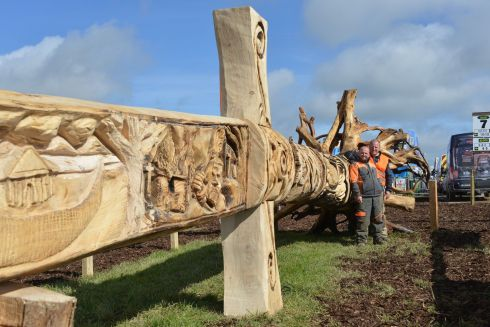 BATTLE READY: Project manager James Doyle, from Tramore, Co Waterford, and carver John Hayes, from Fenor, Co Waterford, relax beside their Viking sword carved from a fallen native Douglas fir tree ahead of the opening day of the 86th National Ploughing Championships in Screggan, Tullamore, Co Offaly. Photograph: Barbara Lindberg.