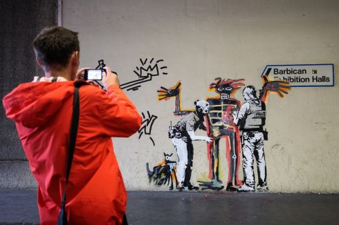 BANKSY: A member of the public takes a photograph of a new work by street artist Banksy by the Barbican Centre in London. The two new murals mark the opening of an exhibition by the late American painter Jean-Michel Basquiat at the centre. Photograph: Jack Taylor/Getty Images
