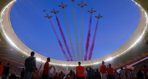 Atlético Madrid fans watch a flyover by Eagle Patrol before the opening game at  Estadio Wanda Metropolitano against Malaga. Photograph: Gonzalo Arroyo Moreno/Getty Images