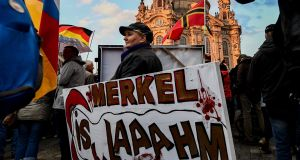 A supporter of the Pegida movement and German right-wing populist party Alternative for Germany holds a banner against   Angela Merkel, in Dresden, on Monday. Photograph: Filip Singer/EPA