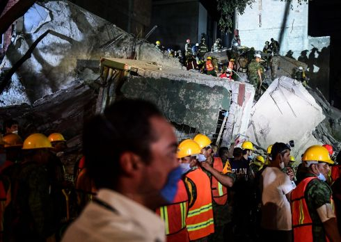 Rescuers, firefighters, policemen, soldiers and volunteers remove rubble and debris from a flattened building in search of survivors after a powerful quake in Mexico City.  Photograph: Ronaldo Schemidt / AFP