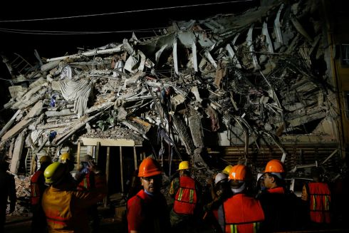 Rescuers work at the site of a collapsed building after an earthquake in Mexico City.  Photograph: Henry Romero / Reuters