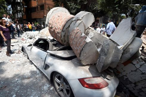 Picture of a car crashed by debris from a damaged building after a quake rattled Mexico City.  Photograph: Alfredo Estrella / AFP