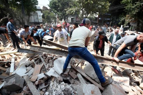 People remove debris of a building which collapsed after a quake rattled Mexico City .  Photograph: Alfredo Estrella / AFP