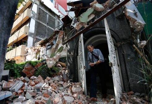A man walks out of the door frame of a building that collapsed after an earthquake, in the Condesa neighborhood of Mexico City. Photograph: Marco Ugarte / AP