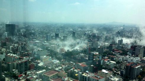 In a view shot through a window of the iconic Torre Latina, dust rises over down town Mexico City during the 7.1 earthquake.  Photograph: Francisco Caballero Gout / AP