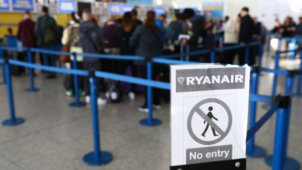 Travellers queue at a Ryanair customer service desk at Stansted. Photograph: Neil HalL/EPA