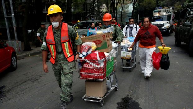 Soldiers carry donations of items for rescue workers and victims next to at a collapsed building. Photograph: Henry Romero/Reuters