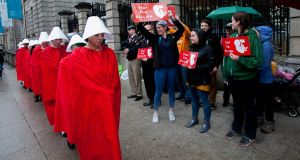 Rosa (For Reproductive Rights Against Oppression, Sexism & Austerity) campaigners dressed as handmaids pass anti-abortion activists at Leinster House. Photograph: Gareth Chaney/Collins
