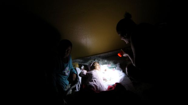 A woman with a flashlight illuminates her baby inside a shelter before the arrival of the Hurricane Maria in Punta Cana. Photograph: Reuters/Ricardo Rojas