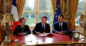 French president Emmanuel Macron signs documents to promulgate a new labour bill at the Elysee Palace in Paris. Photograph: Philippe Wojazer/AFP/Getty Images