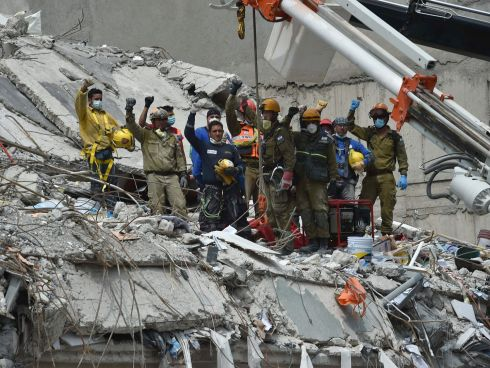 CLENCHED FISTS: Two days after a strong earthquake in Mexico, rescuers and firefighters raise clenched fists in tribute to a man who survived the quake but died before they were able to reach him during the search for survivors, at a flattened building in Mexico City. Photograph: Yuri Cortez/AFP/Getty Images