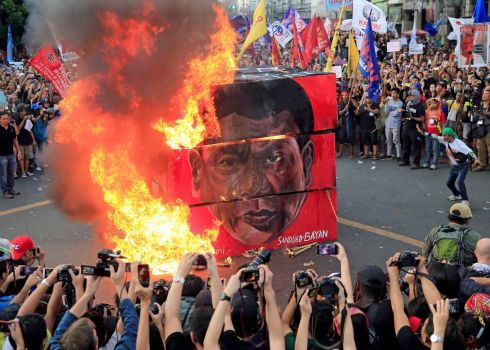 DUTERTE PROTEST: Protesters burn a cube effigy with the image of President Rodrigo Duterte during a national day of protest outside the presidential palace in Manila, Philippines. Photograph: Romeo Ranoco/Reuters