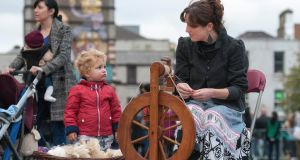 Jean Moran spins yarn from raw fleece, watched by Hans Constable Herriott,  in Smithfield in Dublin as Culture Night gets under way. Photograph: Dave Meehan