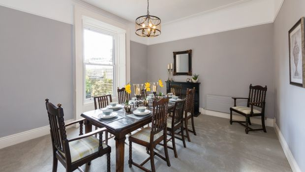 The diningroom at 11 Spencer Villas, Glenageary has a black timber fireplace inset with coloured tiles and uPVC sash windows