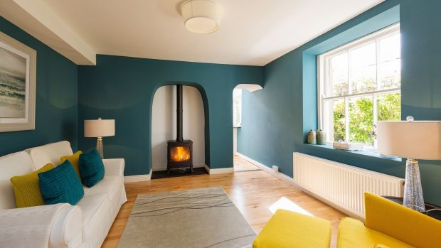 Steps at the end of the hall lead down to a family room, painted teal blue, with a wood-burning stove