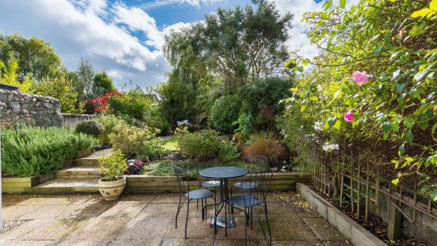 Steps up from the patio in the landscaped rear garden lead to a long, fairly narrow lawn, with raised flowerbeds