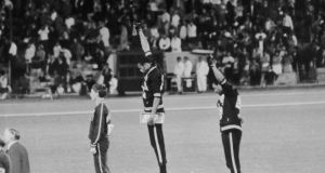 US athletes Tommie Smith (C) and John Carlos (R) raise their gloved fists in the Black Power salute to express their opposition to racism in the USA during the US national anthem, after receiving their medals 17 October 1968 for first and third place in the men's 200m event at the Mexico Olympic Games