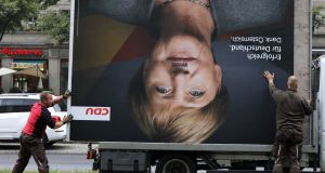 GERMAN ELECTION: Workers in Berlin remove an election campaign billboard showing CDU party leader Angela Merkel, the day after the German general election. Photograph: Christian Mang/Reuters