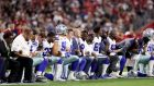 Members of the Dallas Cowboys link arms and kneel before the US national anthem is played at the University of Phoenix Stadium in Arizona. Photo: Christian Petersen/Getty Images