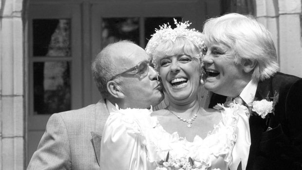 Coronation Street barmaid Bet Lynch (Julie Goodyear) getting a kiss from television groom Alec Gilroy (actor Roy Barraclough), and best man Charles Halliday (actor Tony Booth), after the TV wedding at the Holy Trinity Church in Bolton, Lancashire. Photograph. PA Wire