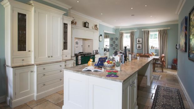 The L-shaped Dalkey Design kitchen/diningroom has a very large granite-topped island unit, a glossy green Aga set into the tiled chimneybreast, and smart cream timber units.