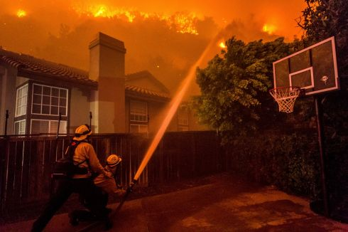CANYON FIRE: Firefighters battle to save homes in Corona, California. Photograph: Watchara Phomicinda/Orange County Register via AP