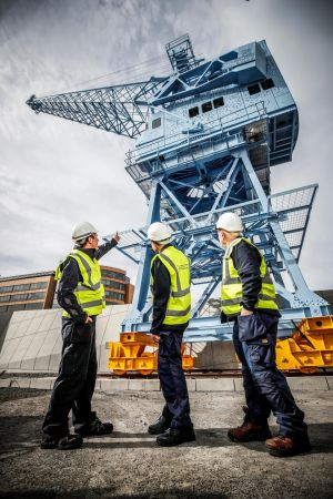 SKY HIGH: former crane operators Tony Forde, Liam O'Brien and Paddy Paisley with the restored Crane 292, a 1960s machine once synonymous with Dublin Port. Photograph: Conor McCabe