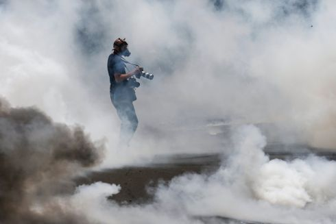 KENYAN PROTESTS: A photographer stands in tear gas during a demonstration against Kenya's electoral commission, which opposition supporters say needs to be reformed before a presidential election can take place on October 26th.  Photograph: Dai Kurokawa/EPA