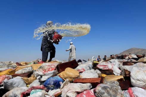 DRUG HAUL: An Afghan man prepares to burn illegal narcotics on the outskirts of Jalalabad. Photograph: Parwiz/Reuters