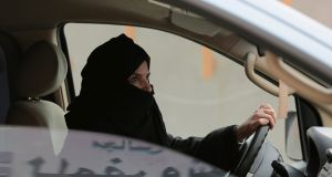 In this 2014 photograph Aziza Yousef drives a car  in Riyadh as part of a campaign to defy Saudi Arabia's ban on women driving. Photograph: AP Photo/Hasan Jamali