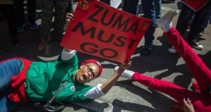 A member of South Africa's Congress of South Africa Trade Unions (Cosatu) waves a sign during a demonstration calling for the removal of South Africa's President Jacob Zuma  in Johannesburg. Photograph: Mujahid Safodien/AFP/Getty Images