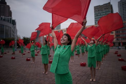 RED FLAGS: A propaganda troupe performs a flag-waving routine outside the central railway station in Pyongyang, North Korea. Photograph: Ed Jones/AFP/Getty Images