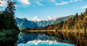 Reflections in Lake Matheson  near the Fox Glacier in  New Zealand which  is seeking Irish truck drivers.
