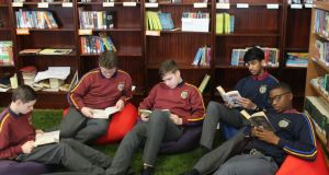 Pupils reading books donated to the library of O'Connell's Secondary School  in Dublin