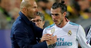 Real Madrid coach Zinedine Zidane shakes hands with Gareth Bale after he was substituted off in their Champions League win over Borussia Dortmund. Photo: Wolfgang Rattay/Reuters