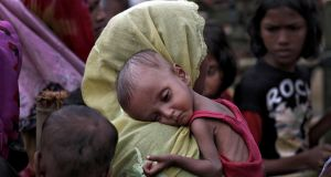 A woman carries an ill Rohingya refugee child through a camp in Bangladesh. Photograph: Cathal McNaughton/Reuters