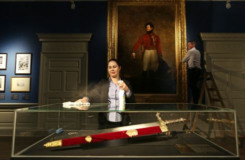 SWORD RETURNS: Cristina Paula Pop cleans a cabinet containing the Irish Sword of State and Darren Lennox adjusts a painting before the launch of the Making Majesty: Building and Borrowing the Regal Image exhibition at Dublin Castle, officiated by chairman of the OPW Maurice Buckley. The exhibition sees the return of the Irish Sword of State to Dublin Castle, lent by Queen Elizabeth from the Royal Collection. Photograph: Julien Behal Photography