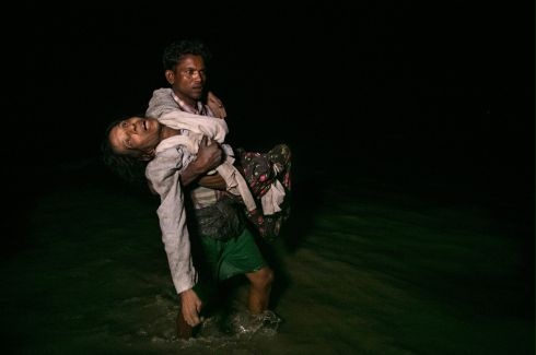 ROHINGYAS FLEE: Sona Banu is carried by Nobi Hossain to the shore of the Naf river as hundreds of Rohingya refugees arrive by boat under cover of darkness at Shah Porir Dwip island, Cox's Bazar, Bangladesh. Hundreds of thousands of Rohingya refugees have fled into Bangladesh since late August during an outbreak of violence in Rakhine state, Myanmar. Photograph: Paula Bronstein/Getty Images