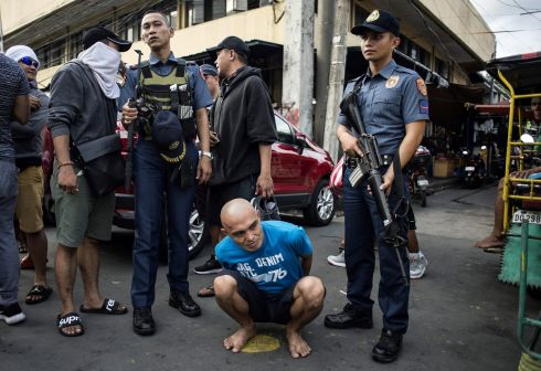 DRUG BUST: An alleged drug dealer is captured by police after an operation in a slum area in Manila. Almost half of Filipinos believe police are killing innocent people while pursuing President Rodrigo Duterte's anti-drugs campaign, according to survey results released on Wednesday. Photograph: Noel Celis/AFP/Getty Images