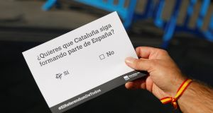 A man holds a dummy ballot before participating in a symbolic vote organised two days before a banned independence referendum in Spain's northeastern region of Catalonia. Photograph: Reuters/Rafael Marchante