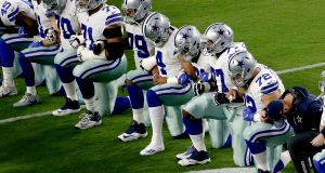 The Dallas Cowboys take a knee prior to the US national anthem, ahead of their NFL game against the Arizona Cardinals, in Glendale. Photograph: Matt York/AP Photo