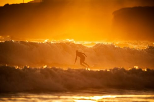WAVES OF LIGHT: A surfer at sunset off Inch beach, in east Co Cork. Photograph: Cathal Noonan
