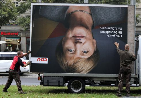 UNEXPECTED OUTCOME: A billboard for the German chancellor, Angela Merkel, is taken away after the country's general election. Photograph: Christian Mang/Reuters
