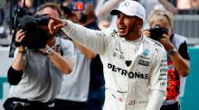Pole position qualifier Lewis Hamilton of Mercedes GP celebrates in parc ferme during qualifying for the Malaysia Formula One Grand Prix at Sepang Circuit. Photograph: Getty Images