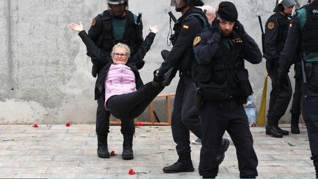 An elderly woman is removed by force as police move in on the crowds.Photograph:David Ramos/Getty Images