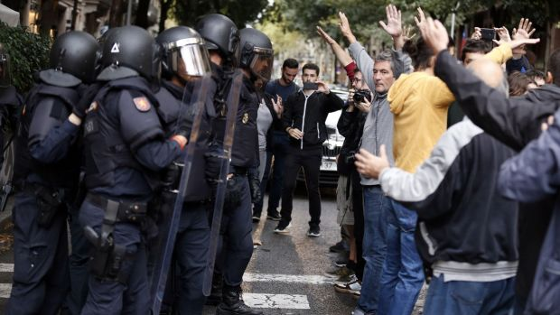 People raise their arms in front of Spanish police after the seizure of ballot boxes in a polling station in Barcelona. Photograph: Pau Barren/Getty Images