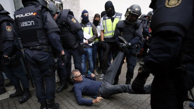 Spanish police clear the entrance of a polling station in Barcelona. Photograph: Pau Barrena/AFP/Getty Images